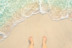 bare foot standing on the white clear water sandy beach and looking to my feet at Phuket island in Thailand