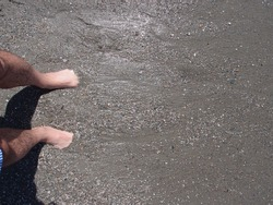 Bare foots in the beach, buried in the dark sand, hairy men legs, with water and waves over the sand.