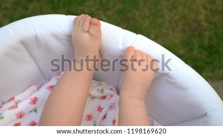 Bare legs of newborn baby. Infant baby in stroller outdoors. Parenting happiness secret. Infants care tips.