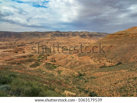 Bare mountainsides with desert agriculture and dirt roads in the valley under a dramatic moody sky in the highlands of western Libya. Adventure travel, tourism, farming and conservation concept. #1063179539