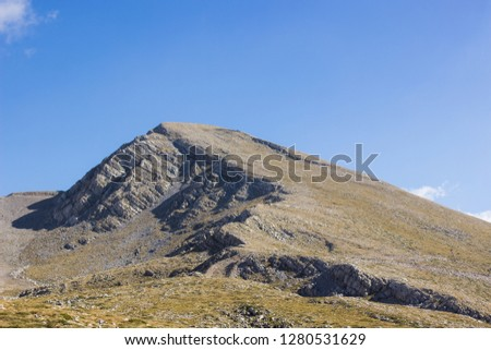 bare steep picturesque lonely mountain peak on empty blue sky background landscape wallpaper view, travel and hiking concept photography