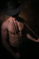 Barechested cowboy wearing hat covering his face holding rope around his neck with defined pecs and muscular sixpack abs