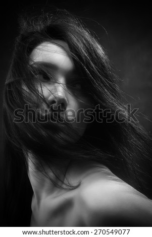 bared woman with fluffy hair looking back monochrome