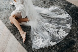Barefoot bride sitting on the floor, wearing a long lace veil.