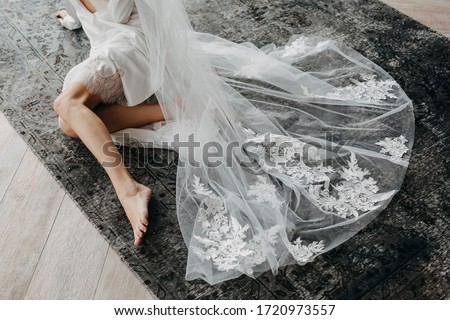 Barefoot bride sitting on the floor, wearing a long lace veil. Stockfoto ©