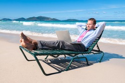 Barefoot businessman working on his laptop on a beach chair relaxing on the shore of an empty tropical beach