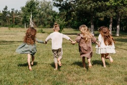 Barefoot children, running on grass in a park, wearing vintage rural clothes.
