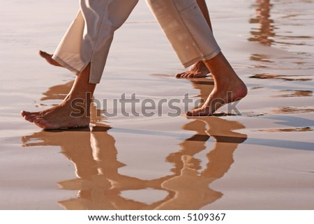 Barefoot couple (feet and legs only) walking on sandy, wet beach