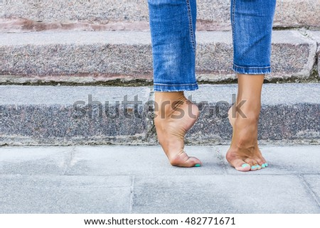 Barefoot dancer foot in jeans and a foot on the background of stone steps. Sexy female legs