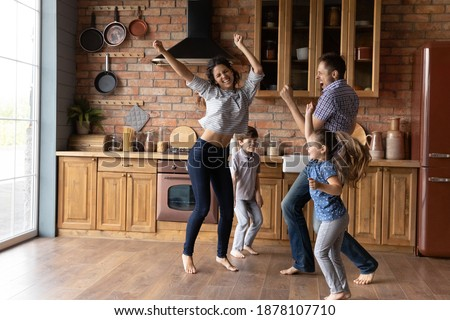 Barefoot dances. Overjoyed millennial family with little daughter son having fun listening to music dancing. Active mom dad and two junior school age kids jump at kitchen celebrate moving to new home