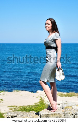 barefoot elegant young woman standing near the sea