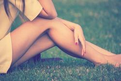 barefoot female legs in grass retro colors