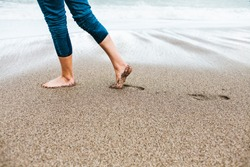 Barefoot girl in jeans walking along the sandy shore. Women's feet on the sand. Walk on the sea coast. A woman in rolled up clothes is walking in cold water.