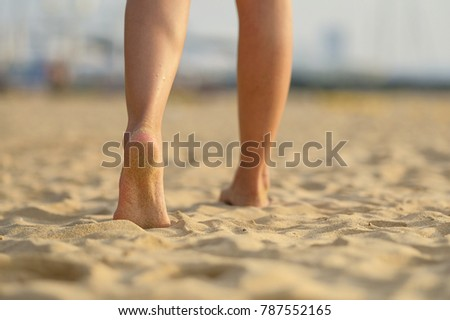 barefoot girl walking on the sand beach with sunset light #787552165