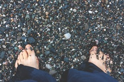 Barefoot on the autumn beach. Unity with nature. The bare feet of a person in blue linen trousers on the wet gravel of the beach.