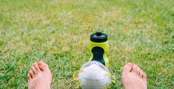Barefoot on the grass in a park with a mask to prevent coronavirus and a bottle of water Returning from outdoor sports. Resting after running.