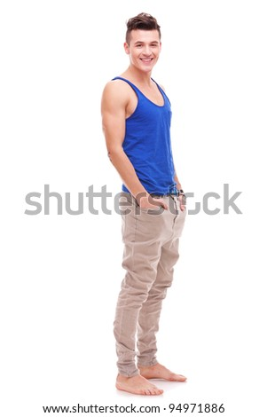 barefoot sexy young man standing with his hands in his pockets on white background - stock photo