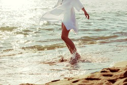 barefoot woman enjoy in sea water in white long shirt, lower body,  side view