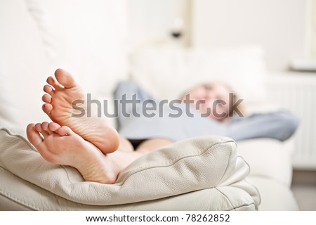 Barefoot Young Woman Lying On Sofa Shallow Depth Of Field