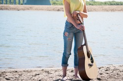 barefoot young woman wearing jeans and yellow shirt standing on beach holding guitar in front of her