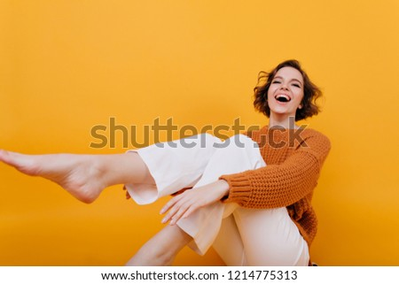 Barefooted blissful european girl enjoying life. Smiling refined lady wears classic white pants fooling around on yellow background.