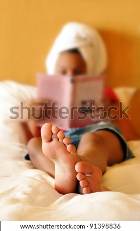barefooted girl in bed reading a book