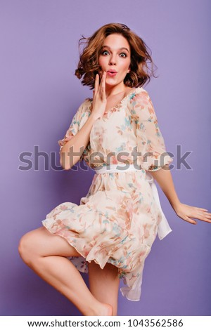 Barefooted graceful girl dancing on purple background with amazed face expression. Lovely young lady in dress with flower pattern posing emotionally in studio.
