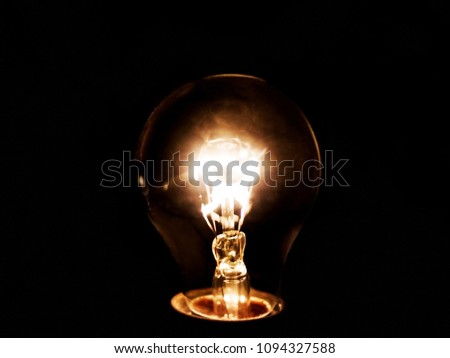 Barely lighting bulb isolated in black color #1094327588