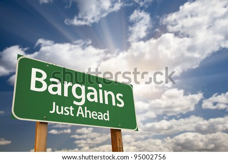 Bargains Just Ahead Green Road Sign with Dramatic Clouds, Sun Rays and Sky. - stock photo