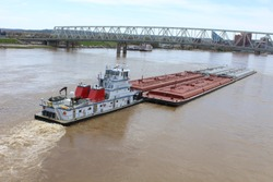 Barge and tug pushing down river