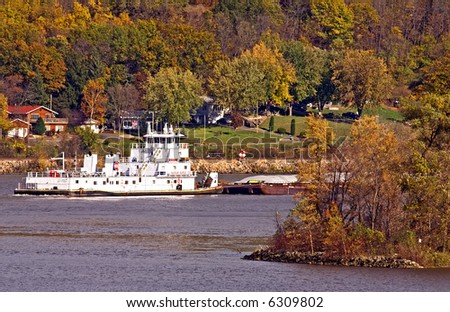 Barge headed down the Mississippi River passing by a colorful fall landscape scene.
