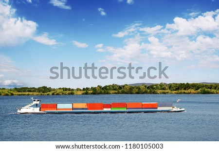 Barge loaded with containers on a big river.