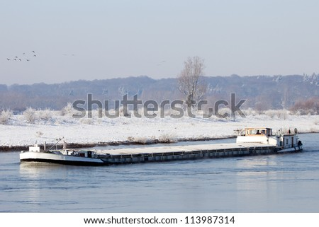Barge on a river during winter