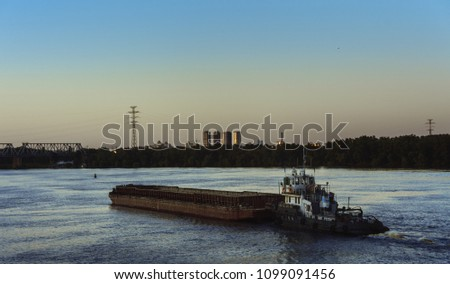 barge tractor moves a barge along the river.Barge is moving forward against cityscape horizon line