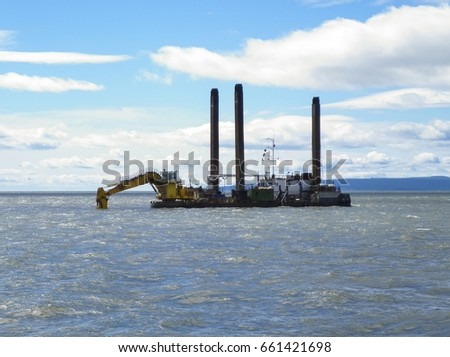 Barge with excavator. Excavator on the barge. Special vessel with a ladle and piles for anchoring on the ground.