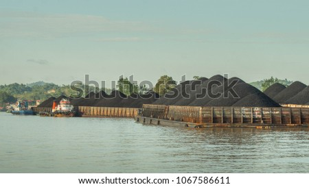 barges full of coal anchored on Mahakam riverbank waiting to be transported #1067586611