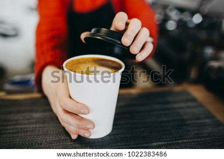 Barista in apron is holding in hands hot cappuccino in white takeaway paper cup. Coffee take away at cafe shop