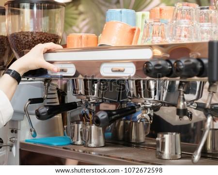 Barista is brewing coffee with professional espresso machine #1072672598
