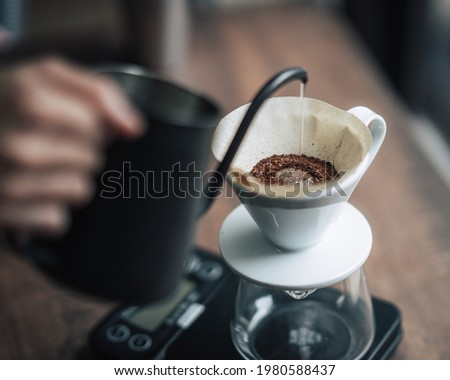 Barista is making drip brewing, filtered coffee, or pour over coffee with hot water and filter paper in coffee shop.vintage tone.