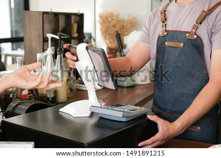 Barista is using the screen to receive orders from customers who are pointing to order coffee.
