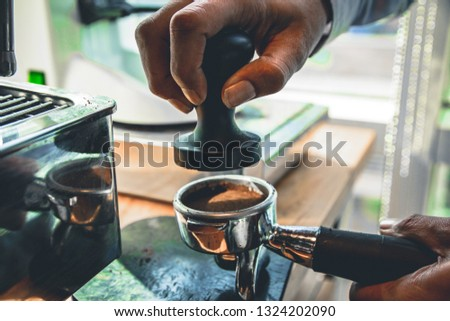 Barista loads the holder for the coffee machine and presses the press