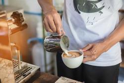 Barista make coffee latte art with espresso machine in cafe vintage color tone. Barista Cafe Making Coffee Preparation Service Concept