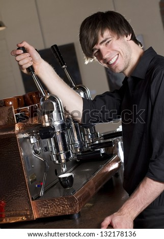 Barista making an espresso a barista smiles at the camera while brewing an espresso working in a cafe.