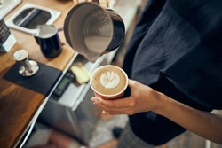 Barista making cappuccino, bartender preparing coffee drink. Coffee cup with latte art