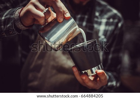Barista making coffee, Bartender pouring milk in to coffee cup in close up view #664884205