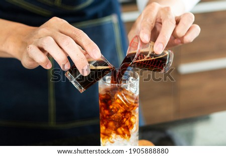 Barista making Ice coffee in a tall glass by pouring brew coffee  over ice on a old rustic wooden table. Young barista pouring cold brew coffee into glass on table. Photo stock ©