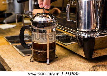 Barista making non traditional coffee in french press, barista coffee preparation service concept.