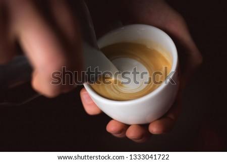 Barista male hands pouring milk and preparing cappuccino latte or cappuccino coffee