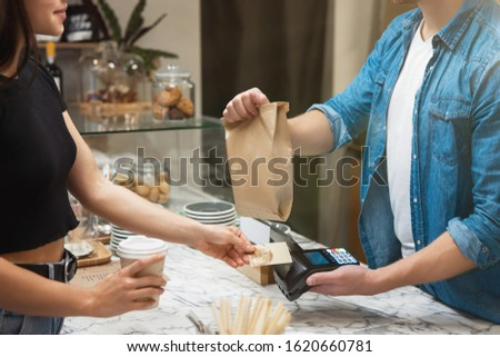 barista man standing behind the bar sells food and drink to woman client for takeaway.