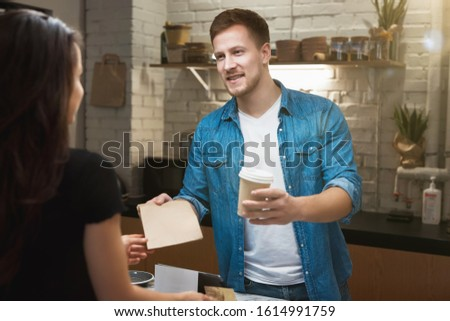 barista man standing behind the bar sells hot coffee drink in paper cup to woman client, holding coffee and papper bag for takeaway.